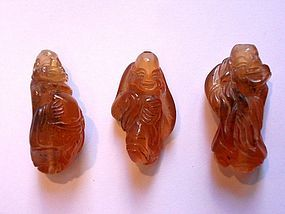 Three amber toggles or beads with Lohan carvings