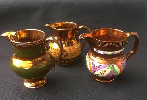 Three Staffordshire copper lustre jugs: green, orange and Gaudy