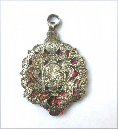 Silver reliquary pendant: St Anthony of Padua, with textile fragment