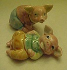Porcelain pig figurines wearing pants and shirt