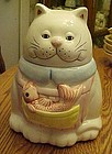 White  ceramic cat with fish in apron cookie jar