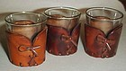 Three shot glasses with leather cozy's or jackets