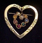 Gold tone heart pin with rhinestone dangle heart center