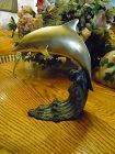 Leaping brass dolphin on bronze wave