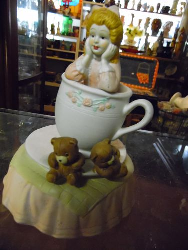 Musical animated girl and teddy bears in a teacup porcelain
