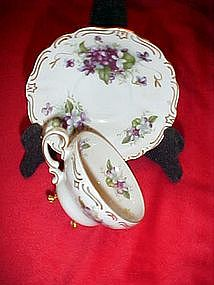 Elegant three legged demitasse cup and saucer, violets