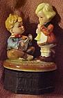 Older Hummel style  ceramic music box, boy and girl