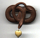 Brooch of a lava snake holding a heart, Ca 1850