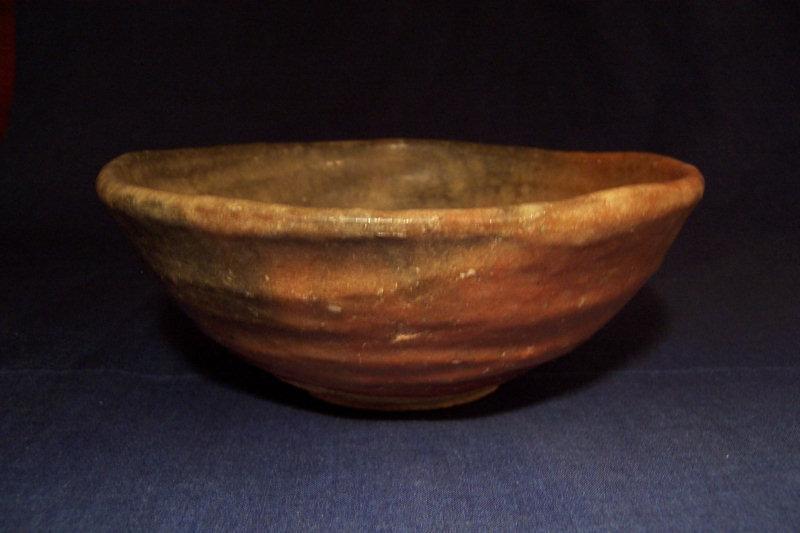 Japanese orange glazed pottery teabowl, marked Kagura