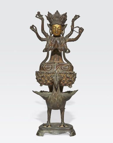 A cast bronze Buddhist or Taoist figure on a peacock
