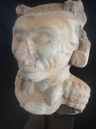 A STRIKING MAYA POTTERY EFFIGY FRAGMENT MOUNTED ON A WOODEN BASE