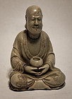 Antique carved steatite figure of a seated Luohan with incised robes