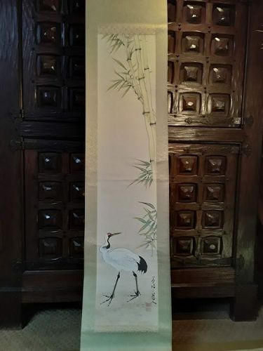 Antique asian scroll of a standing crane with bamboo